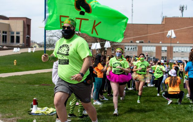 Morale Captains (Green Team) run through the crowed during welcoming ceremonies.