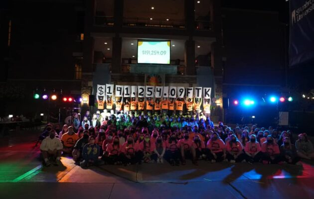 Dancers gather for a photo in front of the Reveal Numbers at the end of the night.